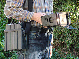 Mobile video lighting unit shown being hand-held, with optional mobile battery pack on a shoulder strap.