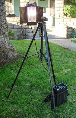 Mobile video lighting unit mounted on large tripod for outdoor use. Light is plugged into one of our mobile battery power packs.